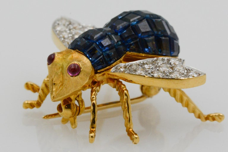 This charming 18k yellow gold French bee pin features 43 square blue sapphires weighing, 3 carats and 22 round brilliant cut diamonds on the wings. The bee also has two cabochon rubies for eyes.