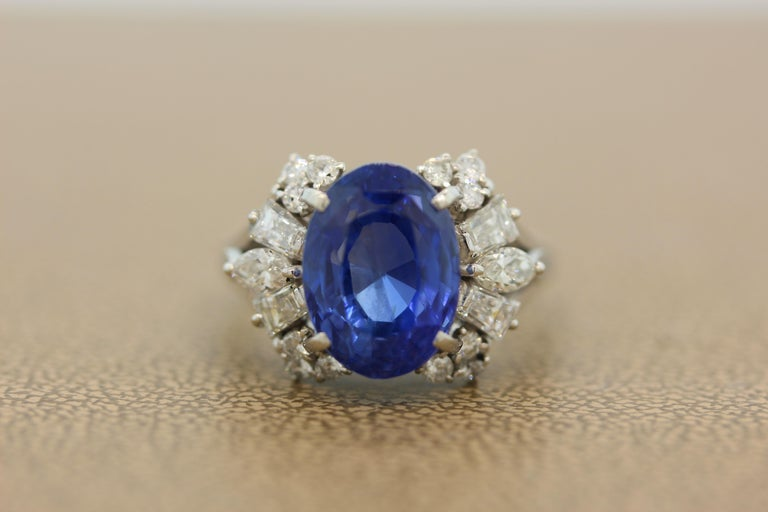 A GIA certified 8.93 carat blue sapphire without heat treatment. The oval cut sapphire has a luscious and even color through the stone, true gem quality. It is accented by a cluster of 1.07 carats of diamonds. Each side of the royal blue sapphire