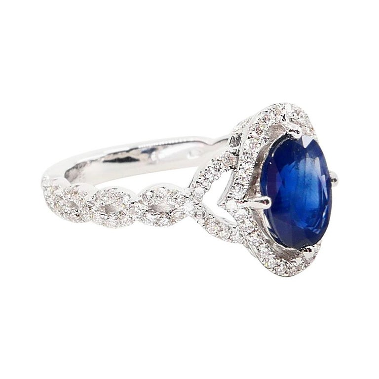 Oval Cut Blue Sapphire and Diamond Twist Ring, 18 Karat White Gold For Sale