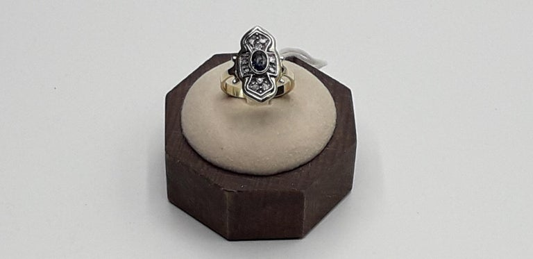 Gold ring with central blue sapphire surrounded by diamonds. Ring size Italian 17 please see the conversion in the table in the picture. This beautiful ring of Italian luxury jewelry 1980s is perfect for a refined and elegant woman.