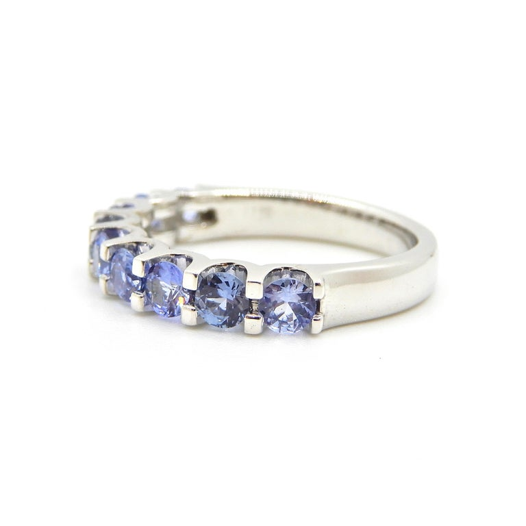 This Blue Sapphire Half Eternity Band 18 Carat White Gold Ring is a beautiful piece to add to your existing all diamond eternity band stack. Set with a rounded band flowing up to row of 9 x round brilliant cut, natural, no heat blue sapphires in a