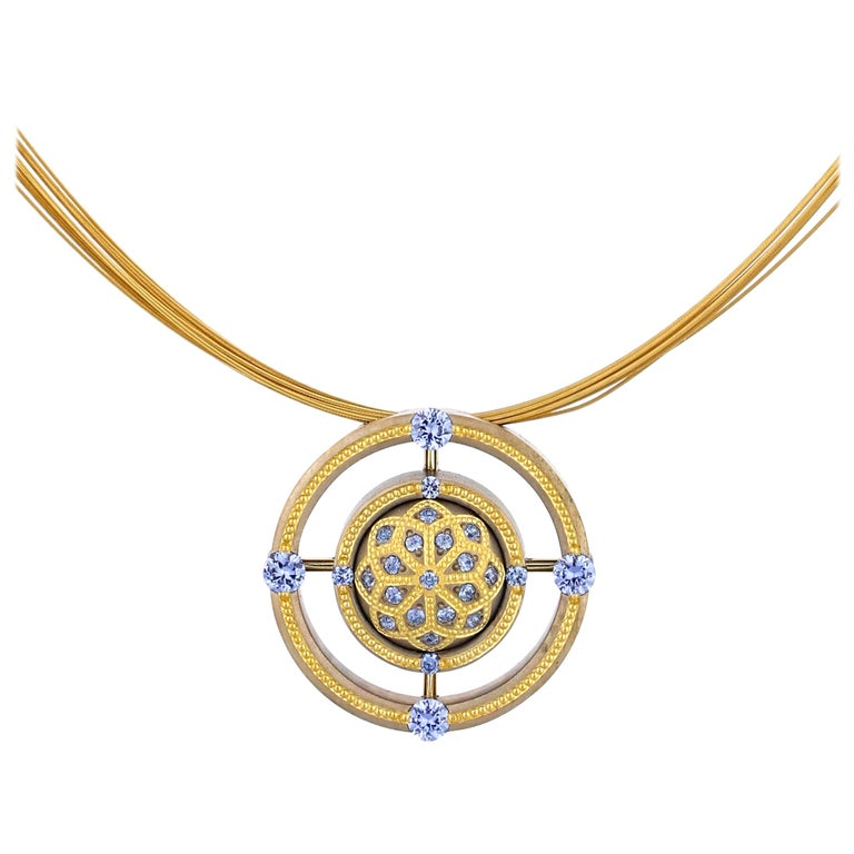 A bejeweled dome of Bronze with an intriguing lotus pattern of 24K Gold shaped inlay and .82 ct. of pastel blue Sapphires. The goldsmith's art of this piece is truly phenomenal. The center dome is encircled by two rings of Bronze with more 24K Gold