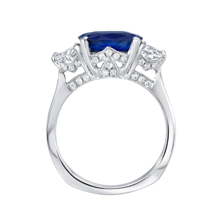 Sapphire ring featuring a vivid Royal Blue, 3.81 carat cushion cut Ceylon Sapphire, flanked by pair of half moon diamonds weighing a total of 0.89 carats, and adorned by a total of 0.28 carat round brilliant diamonds. This sensational platinum,