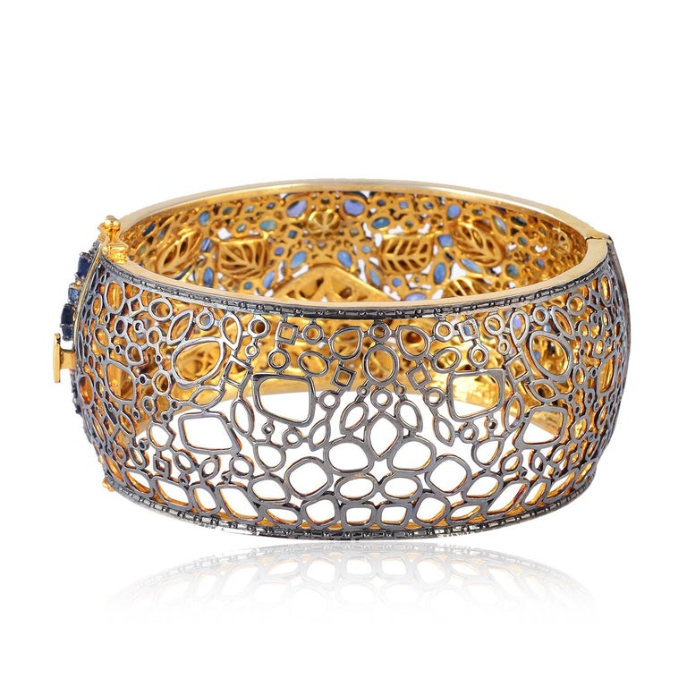 A stunning statement cuff handmade in 18K gold and sterling silver. It is set in 17.23 carats blue sapphire and 9.49 carats rose cut diamonds. Clasp Closure  FOLLOW  MEGHNA JEWELS storefront to view the latest collection & exclusive pieces.  Meghna