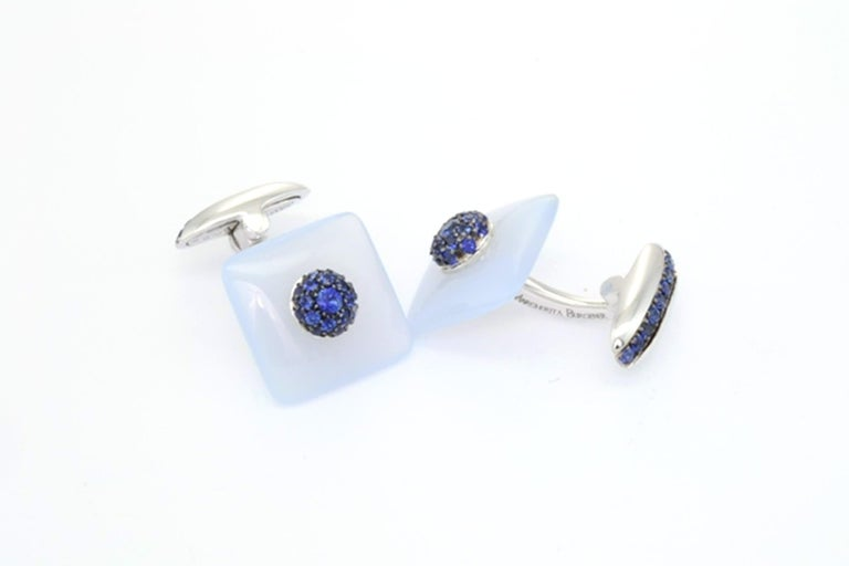 Designed and handcrafted in Margherita Burgener workshop, the refined cufflinks are realized in white gold set with blue sapphires. The light blue stone, squared shaped, slightly bombé, is natural chalcedony. It is a unisex piece of jewelry. They