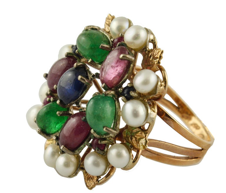 Fabulous fashion ring in 9K rose gold and silver composed of blue sapphires, rubies and emeralds in the center surrounded by little pearls and gold detailes Blue Sapphires, Rubies, Emeralds 7.38 ct  Pearls 0.6 g     4/5 mm Total weight 8.8 g  RF +