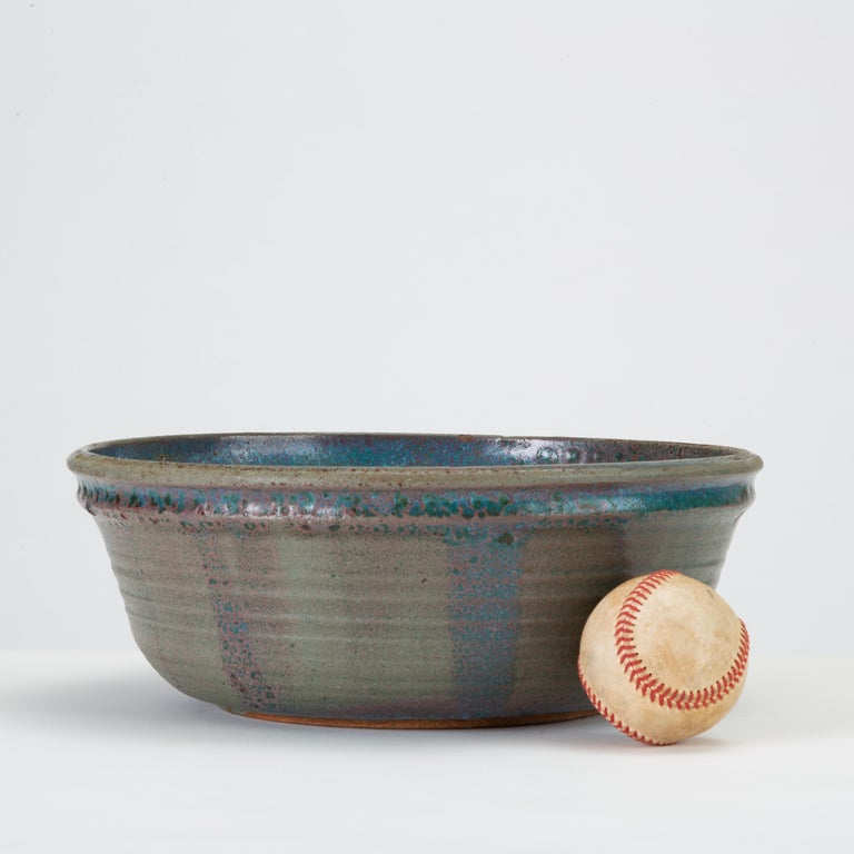 A wheel-thrown studio pottery bowl with a flat bottom and steep sides. A double lip is highlighted by a vibrant strip of cobalt glazing; the bowl is glazed all over in a deep blue with lighter speckled accents. Subtle blistering adds a rustic