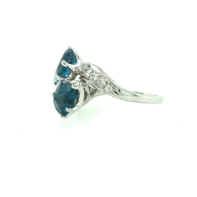 One 14 karat white gold estate ring set with two 7.5x10mm pear shaped blue topaz and eight brilliant cut diamonds, 0.20 carat total weight with matching H/I color and SI clarity. The shank measures 8.30mm near the top of the ring and tapers to 1.60