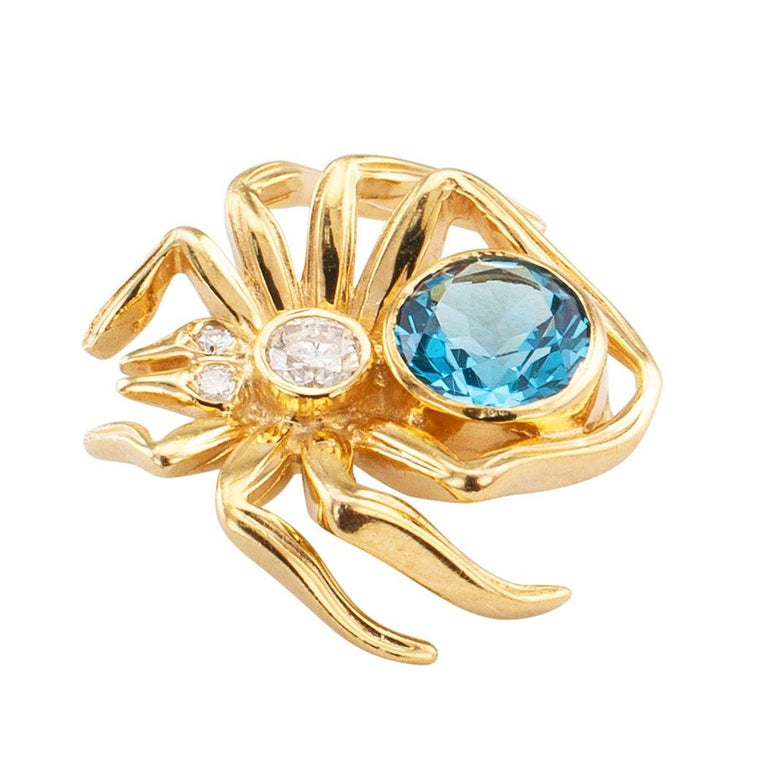 Blue topaz diamond and gold spider brooch circa 1970. The figural design depicting a spider, its body set with a large round blue topaz and three smaller round brilliant-cut diamonds totaling approximately 0.12 carats, crafted in 14-karat yellow