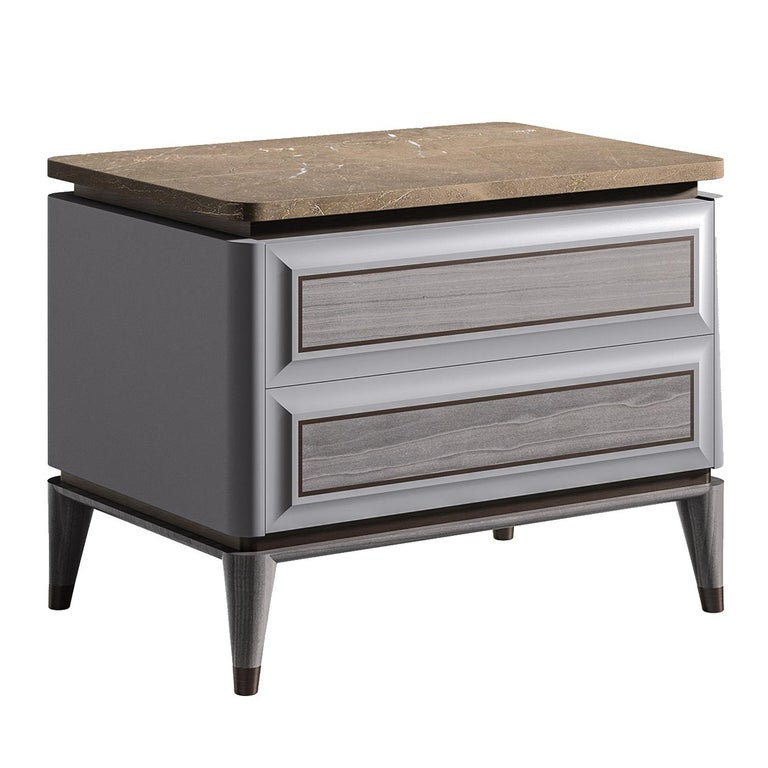 A Classic Silhouette with contemporary flair, this night table features a sleek wood frame with an elegant gray finish and two drawers with raised front panels and brown profiles that recall the metal ferules of the four conical feet. The striking