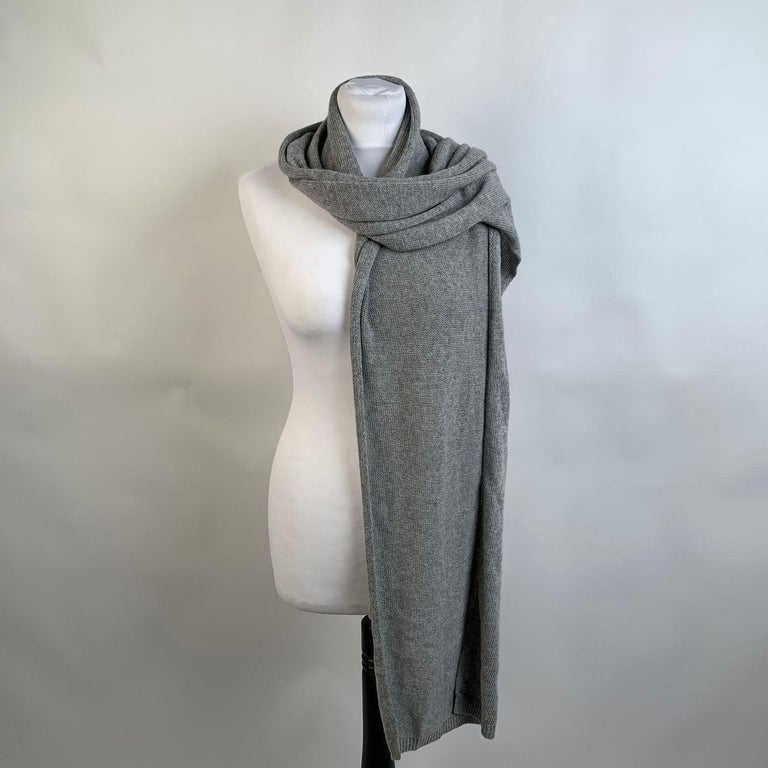Blumarine wrap scarf in gray color. It features B letter, made of rhinestones. Composition: 40% Nylon, 40% Viscose, 10% Silk, 10% Cashmere. Made in Serbia. Width: 16 inches - 40,6 cm - Lenght:82 inches - 208,2 cm     Details  MATERIAL: