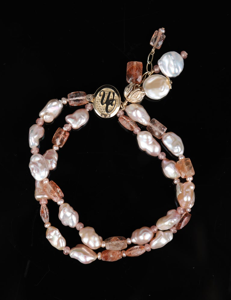 Two strands of blush, Keshi freshwater pearls, faceted sunstone rectangles, round gems of rhodochrosite and freshwater pearls come together with White Orchid Studio's logo clasp in 14kt yellow gold.  This bracelet is enhanced by three tassel