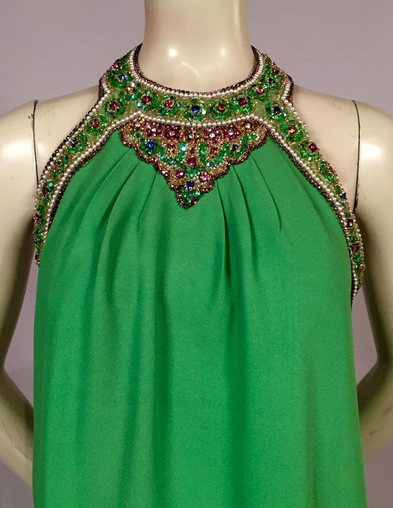 Bob Bugnand has used the most spectacular jewels to decorate the halter neckline of this bright green crepe evening dress. Pearls and prong set pink beads are used to trim all of the edges. A rainbow mix of colors and beads fills every speck of