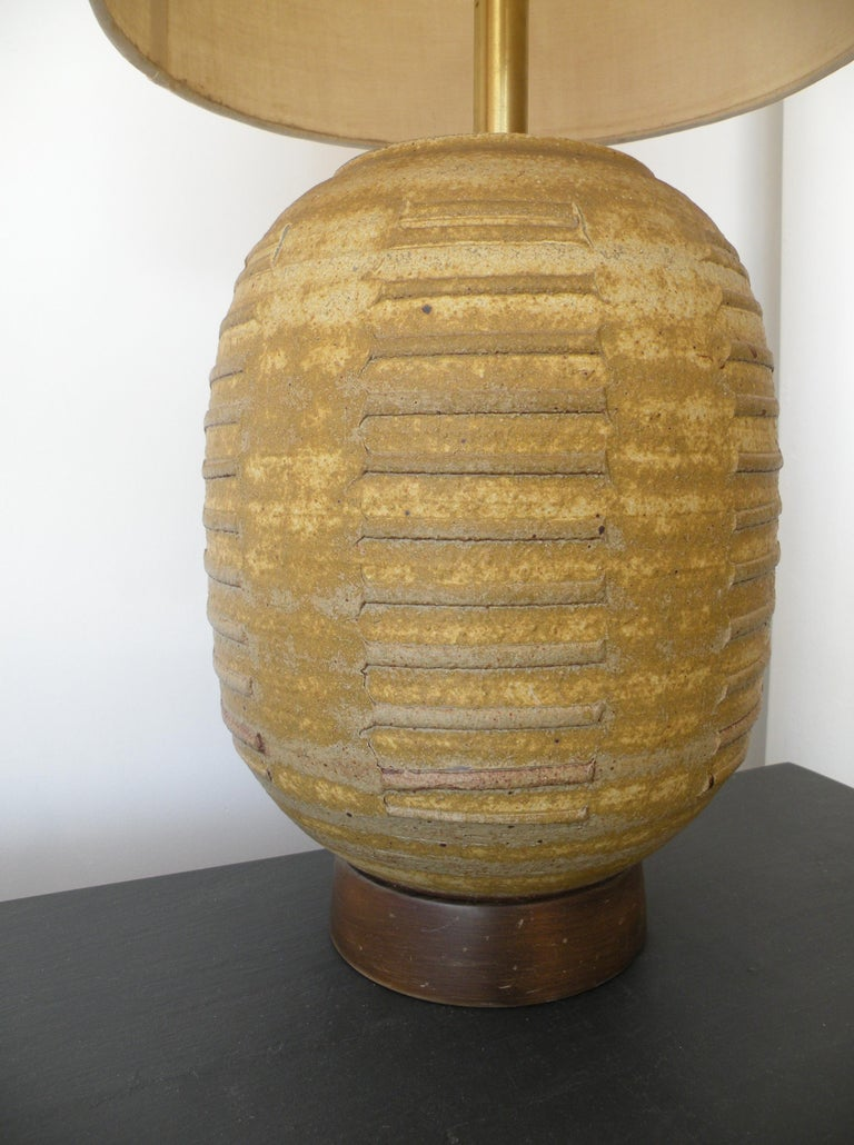 Wheel thrown and texture decorated Studio Pottery table lamp by artisan Bob Kenzie for his workshop Affiliated Craftsmen. A Classic example of the 1960s California Craft movement. Dual earth tone brown and yellow glazed earthenware body on walnut