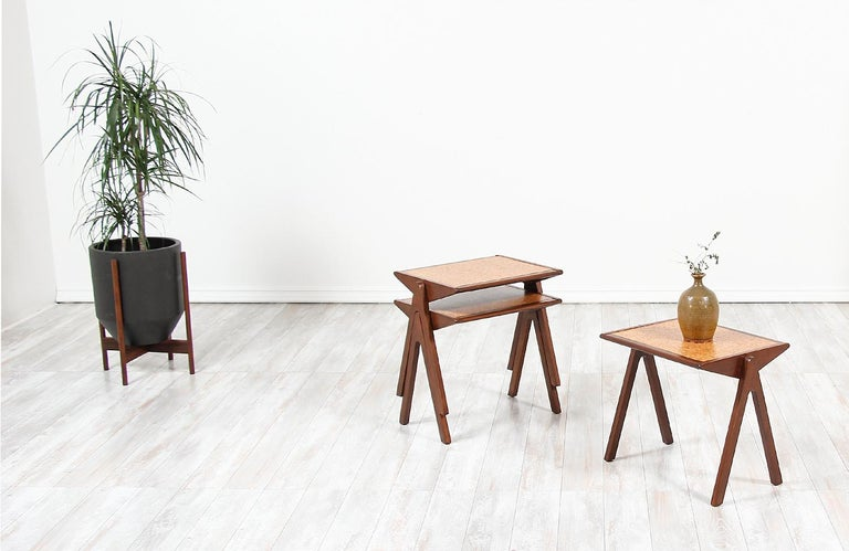 A stylish set of nesting tables designed by Bob Roukema for Jon Jansen in New Zealand, circa 1950s. This stunning set of three nesting tables feature a walnut-stained mahogany frame with its original cork tiled design on rectangular tops and compass