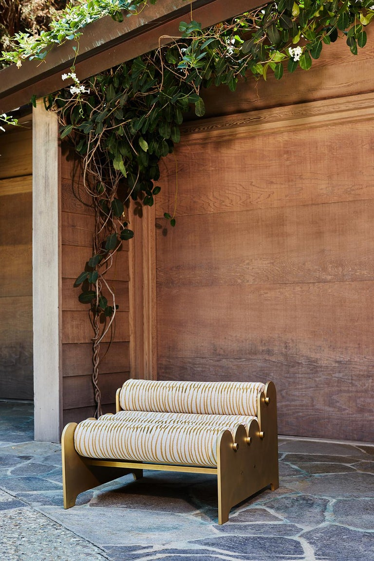 A series of bolsters are threaded between two aluminum rails that evoke the waves of the Pacific. The Bobbin bench is suitable for indoor or outdoor use. Stainless steel rods thread through each outdoor quality cushion and connect the patinated
