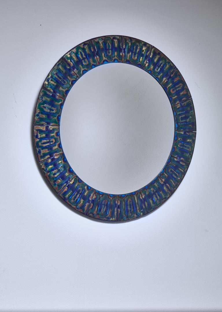 A round wall mirror by Danish designer Bodil Eje (1931-2006). The mirror has a frame made of polychrome enameled copper plates with a beautiful pattern.  Signed on the reverse by the artist.