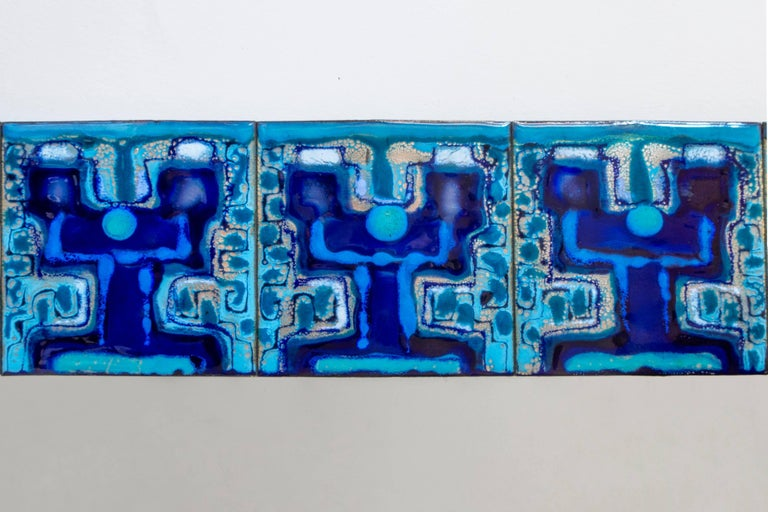 Composed of enameled plates hand-painted by Danish artist Bodil Eje. The repeating pattern displays richly variegated blue, turquoise, indigo, and colorless enamel, surrounding a colorless rectangular mirror glass.   Richly patterned and in