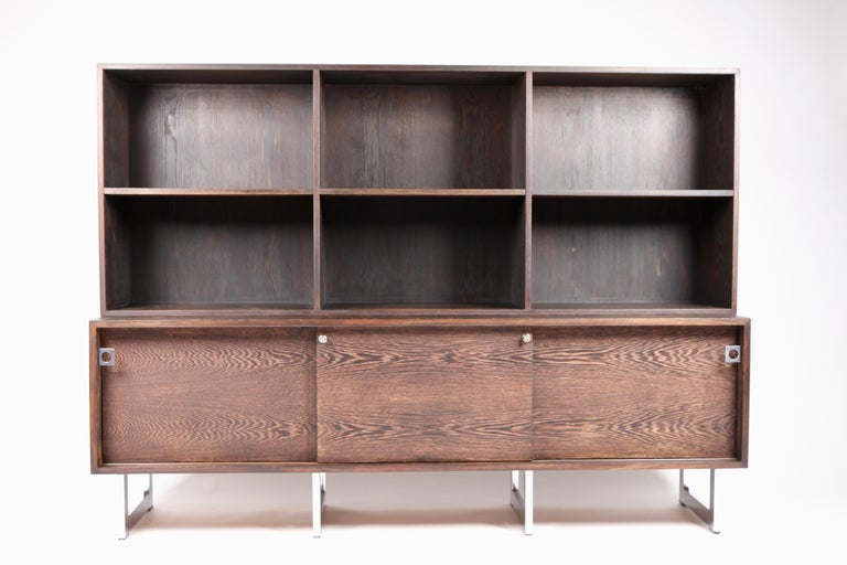 Bodil Kjær, freestanding sideboard with bookshelf in Wenge and chromed steel, executed by E.Pedersen & Son a-s, in the 1960s. Signed with paper label. The front is divided in 3 sliding doors. The credenza is freestanding with Wenge
