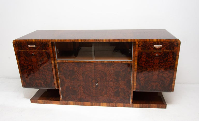Bohemian buffet or sideboard in walnut veneer from the Art Deco period. It was made in the 1930s. It features a very simple and practical design. Standing on a massive rectangular base. Consists of two drawers with chromed handles and two side