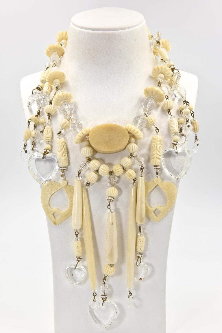 From a Miami socialite's estate, this necklace and matching earrings  are truly a statement piece.  Made in the 1980's, the necklace has carved and smooth bone pieces with gold tone bead accents as well as facetted crystal beads and hearts.    The