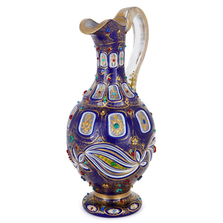 This beautiful glass jug (or ewer) was created in the late 19th century in Bohemia (modern-day Czech Republic). Antique Bohemian glass is prized for the exceptional quality of its craftsmanship and ornamentation. This jug will make a wonderful