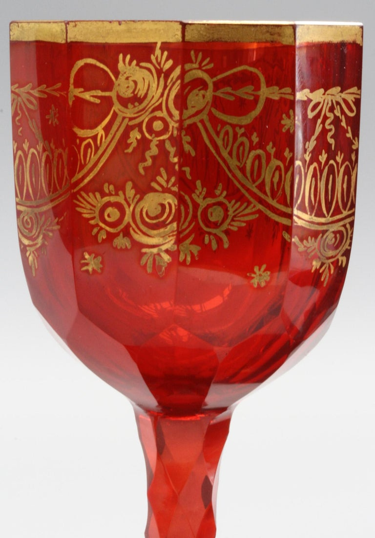 A very rare set Bohemian ruby red colored wine glasses with gilded patterning to the body and foot and dating from the early 19th century around 1810/20. These stylish glasses have wide rounded slightly domed feet decorated with small gilded star