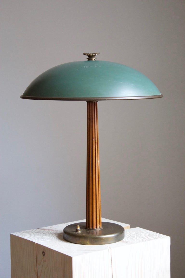 A modernist table lamp or desk light. Produced by the iconic Swedish lamp maker Böhlmarks. Produced in 1935. Features engraving in Swedish, with dating.  Features a finely sculpted lacquered wood handle on a brass rod and base, original lacquered