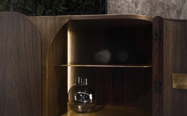 A contemporary cabinet, perfect for use as a bar, designed by the renowned architect and furniture designer Maurizio Manzoni. The use of wood and brass presented in their unaltered natural finishes celebrates the senses. The piece features lacquered