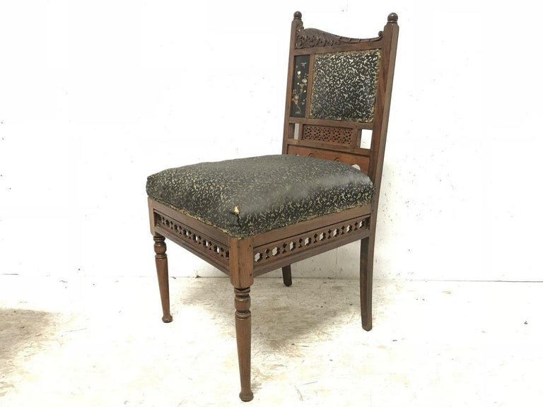 Bombay Art Furniture Co. An Anglo-Japanese side chair with turned finials at different heights and a sweeping carved acanthus leaf scrolling down. An inset lacquer panel with a bird hovering above floral details with Mother of Pearl inlays.