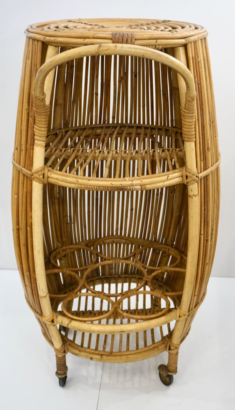This vintage Mid-20th Century Italian barrel shape bar cart on brass casters, in excellent condition, is handcrafted in natural rattan from the Far East, the interior fitted with a middle shelf and 7 bottle holders. The ease of pulling this bar