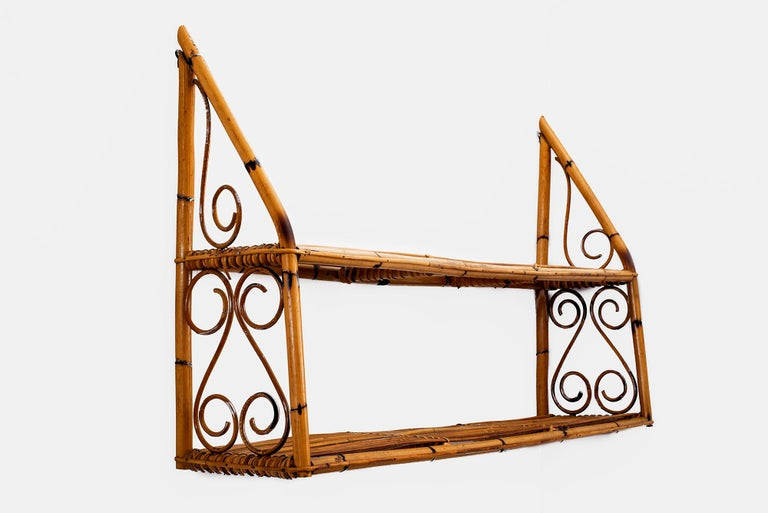 Whimsical rattan wall shelf by Bonacina, Italy, 1950s. Features 2 shelves with decorative design on sides.