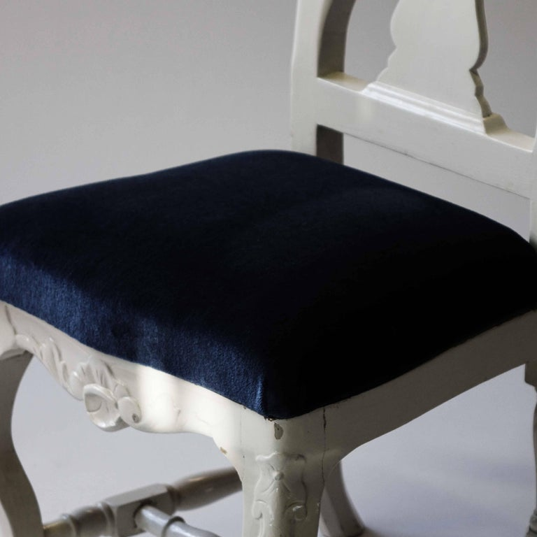 White painted chairs with blue velvet seats in a set of four.