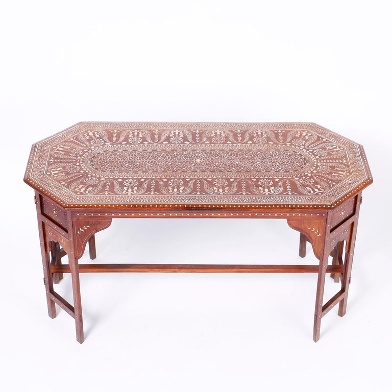 Anglo Indian mahogany coffee table with an elongated octagon form, featuring a top having a center panel with elaborate inlaid floral bone designs emanating from a center button inside repeating graceful tree of life designs. The base has eight legs