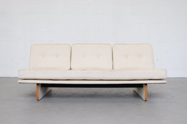 Newly re-upholstered bone white 3-seat Kho Liang le sofa with white laminated plywood base. Base is original and shows some wear consistent with age and use.