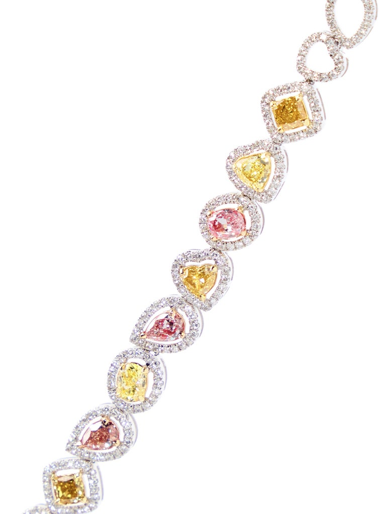 Fancy colored diamonds in a myriad of shapes grace this extraordinary bracelet.   The bracelet is made in 18kt white gold and is set with 12 mixed fancy color cut diamonds weighing 1.98 carat and 1.26ct round brilliant cut diamonds. The 15 openwork