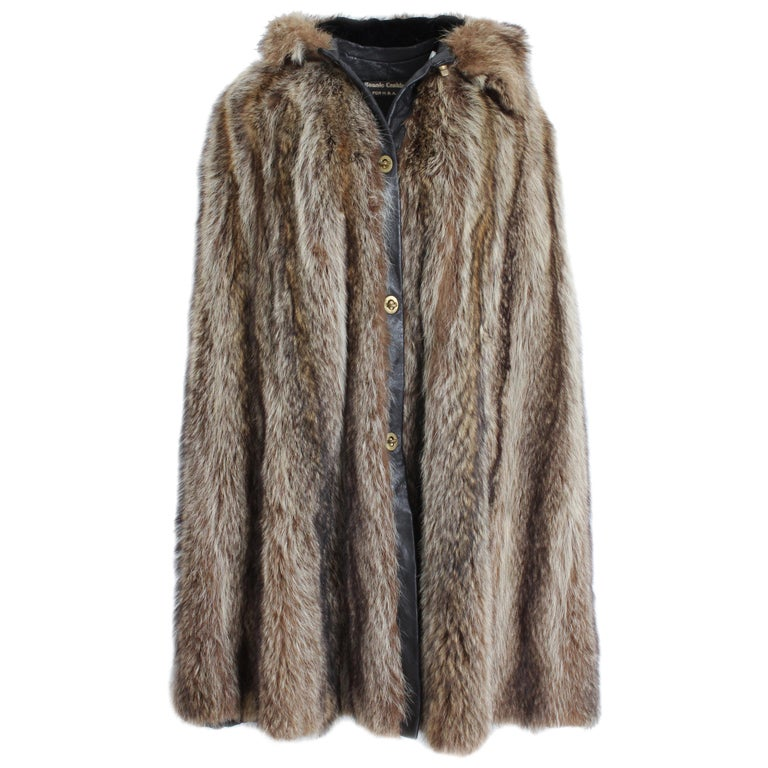 Exquisite Bonnie Cashin for HBA Furs Hooded Raccoon Fur Cape, circa 1974.  Lined in black fabric, it fastens with Bonnie's signature brass turn locks and is trimmed in brown leather.  Arm holes feature hidden interior pockets.  Preowned/vintage with