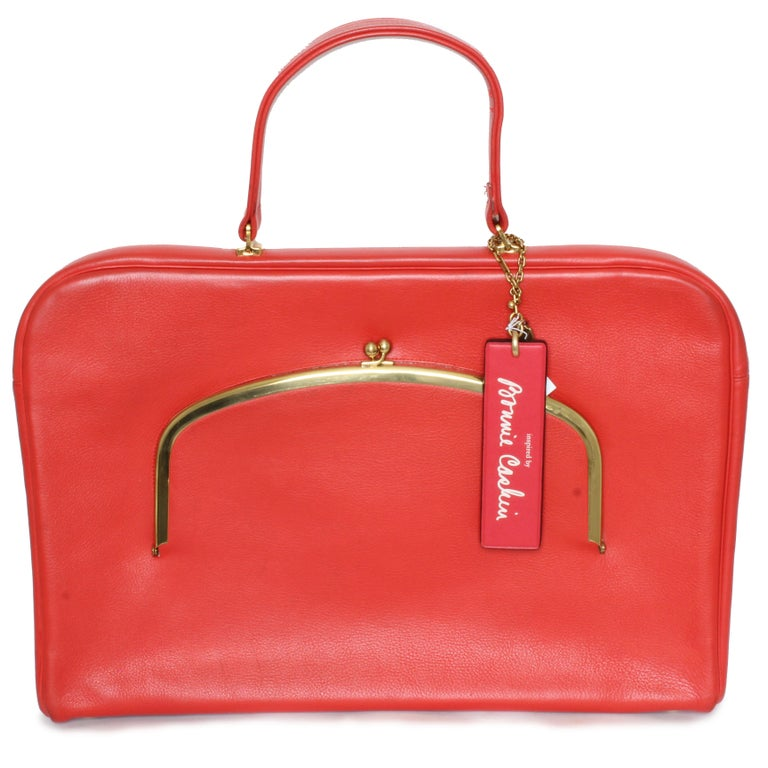 Vintage Bonnie Cashin for Coach 'Cashin Carry' leather attache or briefcase bag. Classic style and vibrant color. Red leather exterior with orange tonal qualities, and lined in Bonnie's signature striped fabric. Zipper main compartment has push lock