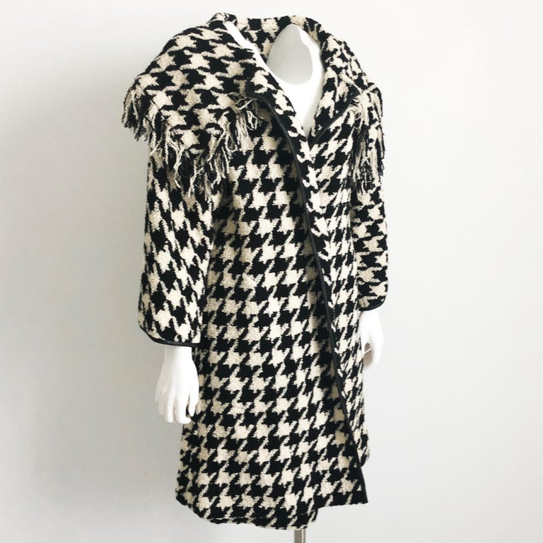 This fabulous ensemble was designed by the mother of American sportswear, Bonnie Cashin. Made from an amazing large houndstooth boucle wool, the jacket is trimmed in black leather & features a huge shawl collar with fringe.  The pencil skirt hugs
