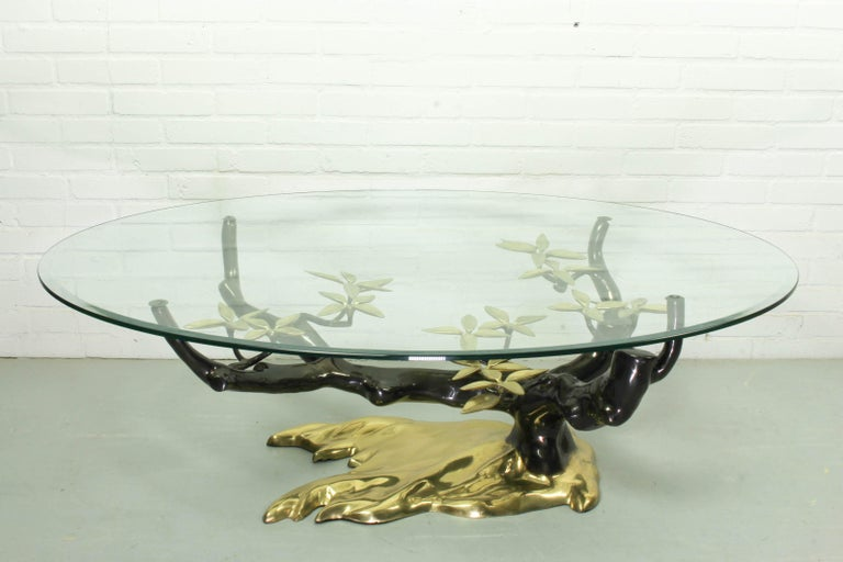 Magnificent Hollywood Regency coffee table in brass Willy Daro, 1970s. The very heavy brass base is shaped as a bonsai tree and topped with an oval glass top with bevelled edge. Dimensions: 42cm H, 130cm L and 90cm D.