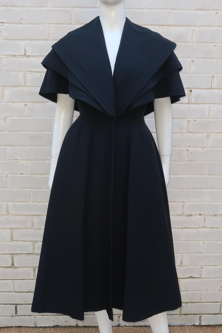 This amazing piece sold through Bonwit Teller, Philadelphia, C.1950, and is intended to be an evening coat but it could easily turn heads as a dress all on its own.  The heavy weight black silk faille fabric is tiered at the bodice providing a
