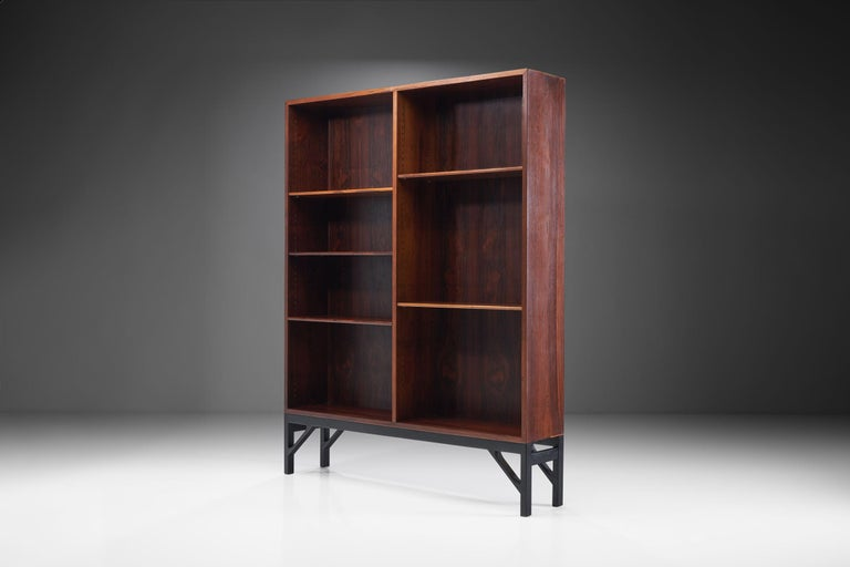 This impressive bookcase designed by Børge Mogensen reflects the Danish designer's aesthetic that was clean and highly functional, creating pieces that stand out despite their restrained design.  The bookcase is made of rosewood with a beautiful
