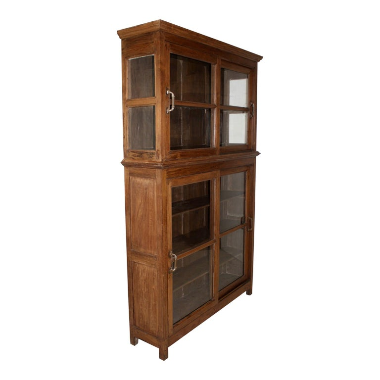 This rustic bookcase features four sliding glass doors, 5 inch door pulls, and block feet. The top has glass sides and one permanent shelf. The base has wood sides and three shelves, which include upper and lower removable shelves and a permanent