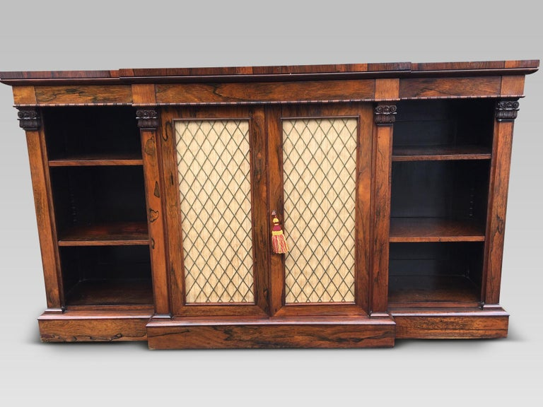 Fine quality English rosewood bookcase from the Regency period. This delightful bookcase has strongly grained rosewood veneers, crisp features and a deep rich finish with patination. There are 6 adjustable shelves. The central breakfront has a