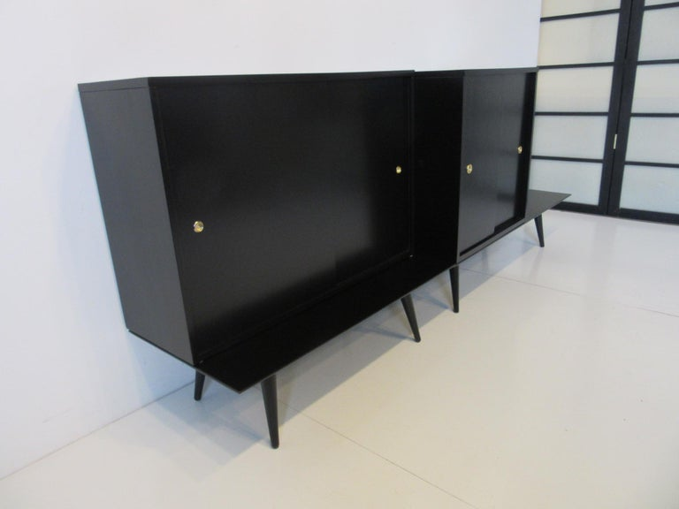 A four piece cabinet set sitting on two bench bases with conical legs, having one bookcase with sliding doors and a storage chest cabinet also with sliding doors finished in satin black and having brass finger pulls . In solid wood construction