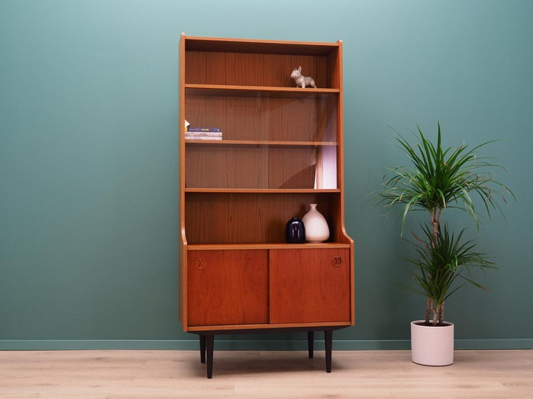 Brilliant bookcase, library from the 1960s-1970s. Scandinavian design, Minimalist form. Furniture finished with teak veneer. The bookcase has three shelves, a glass door and a shelf behind a sliding doors. Maintained in good condition (small bruises