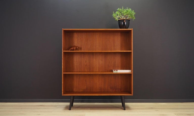 Classic bookcase / library from the 1960s-1970s. Scandinavian design, Minimalist form. Surface of the furniture finished with teak veneer. Bookcase has two shelves with no possibility of adjustment. Preserved in good condition (minor bruises and