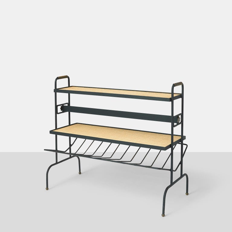 Magazine rack by Jacques Adnet A unique magazine rack or bookstand by Jacques Adnet with two faux wicker horizontal shelves and a lower rack with angled metal support for additional books to face each side. On each side of the metal rack is brass