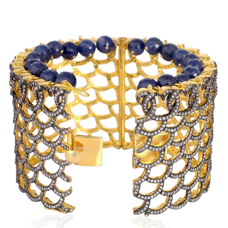 Bold and distinctive, a stunning statement cuff set in blue sapphire & pave diamonds. The Cuff is framed by signature 13.26 carats diamond pave arches. It is further accentuated with 103.8 carats of blue sapphire stone to create a dazzling dangle.