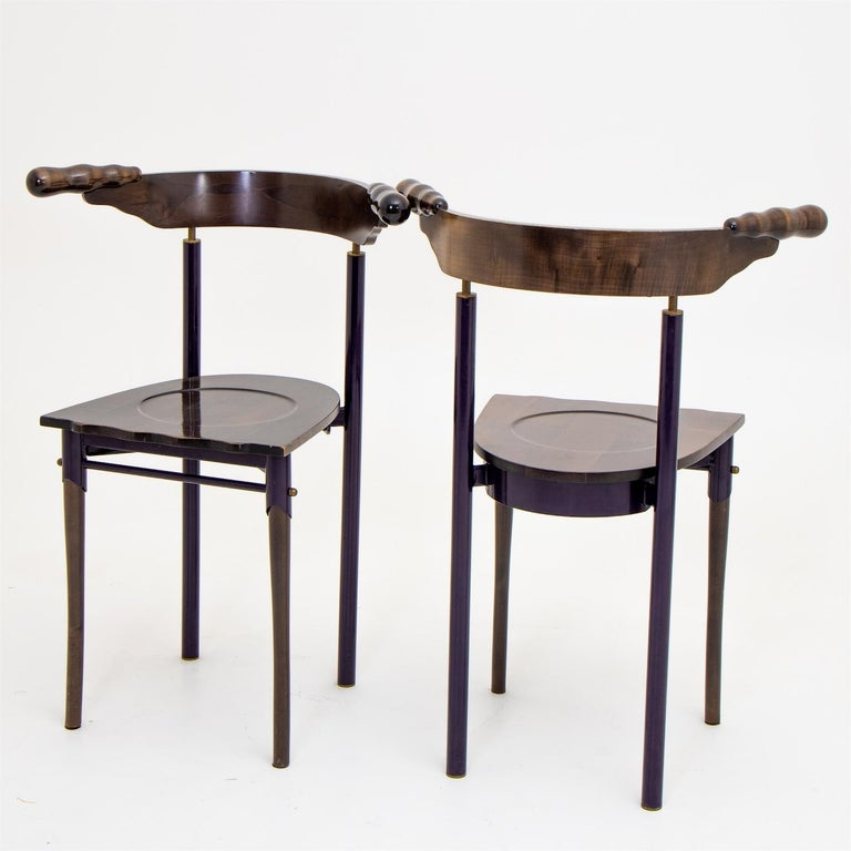 Two designer chairs designed by Borek Sipek for Driade in Italy. The backrest, seat and front legs are made of wood, and the metal frame appears deep purple in most lighting conditions. The rounded backs end in organically shaped knobs and the seat